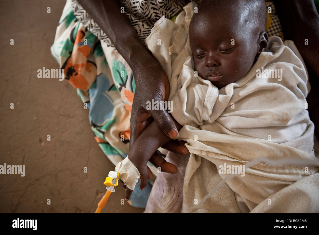 A mother holds her young child who suffers from dehydration in a hospital in Amuria, Uganda. - Stock Image