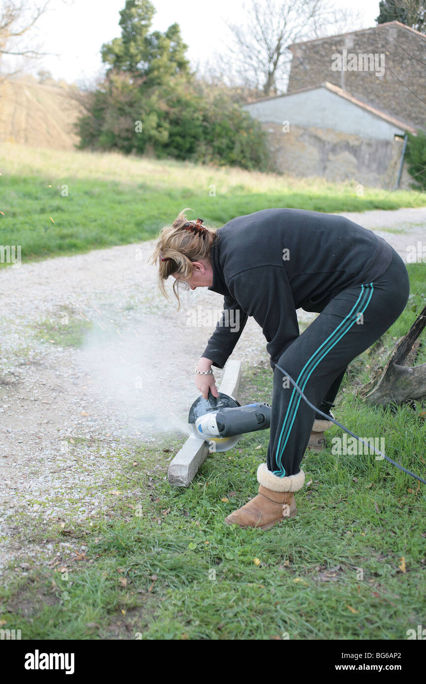 Woman using an angle grinder - Stock Image