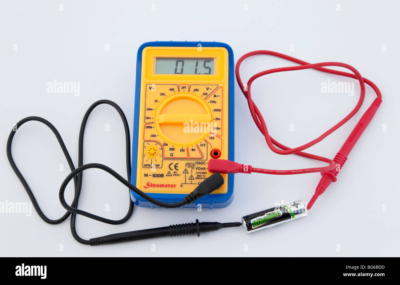 Digital multimeter measuring AA battery voltage on a white background. - Stock Image