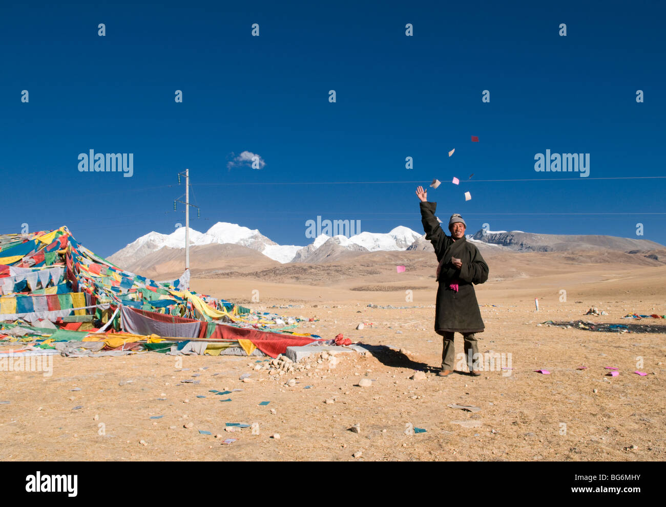 A  Tibetan man throws paper wishes and prayers into the wind in Tibet - Stock Image