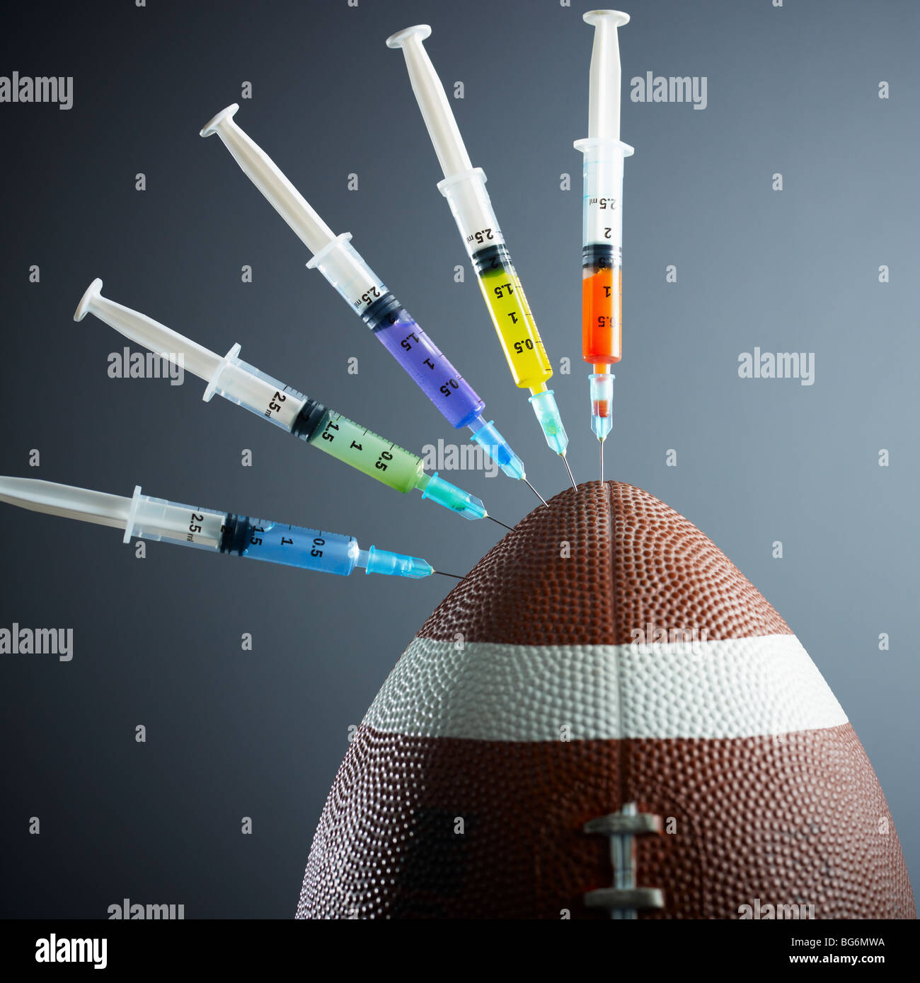 five syringes threaded in american football ball. - Stock Image