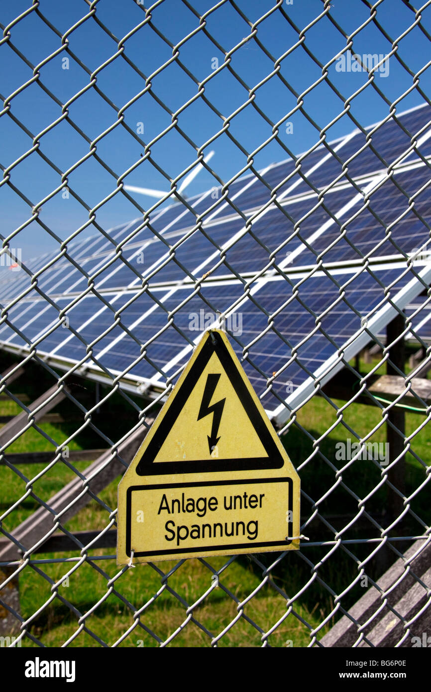 Danger sign and photovoltaic solar panels for electricity production, Germany - Stock Image