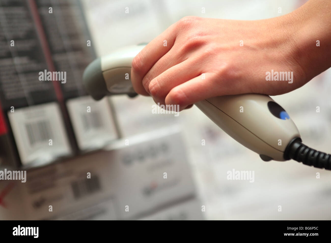 Store. Barcode reader in the hand of the girl. Shallow DOF. - Stock Image
