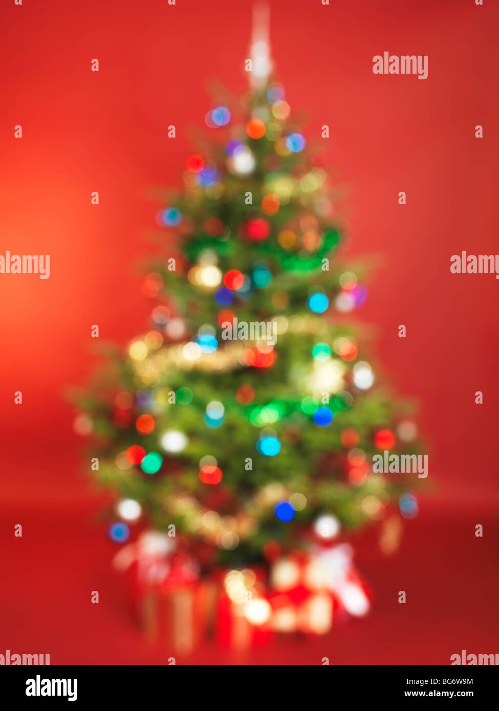 Out of focus decorated Christmas tree isolated on red background - Stock Image