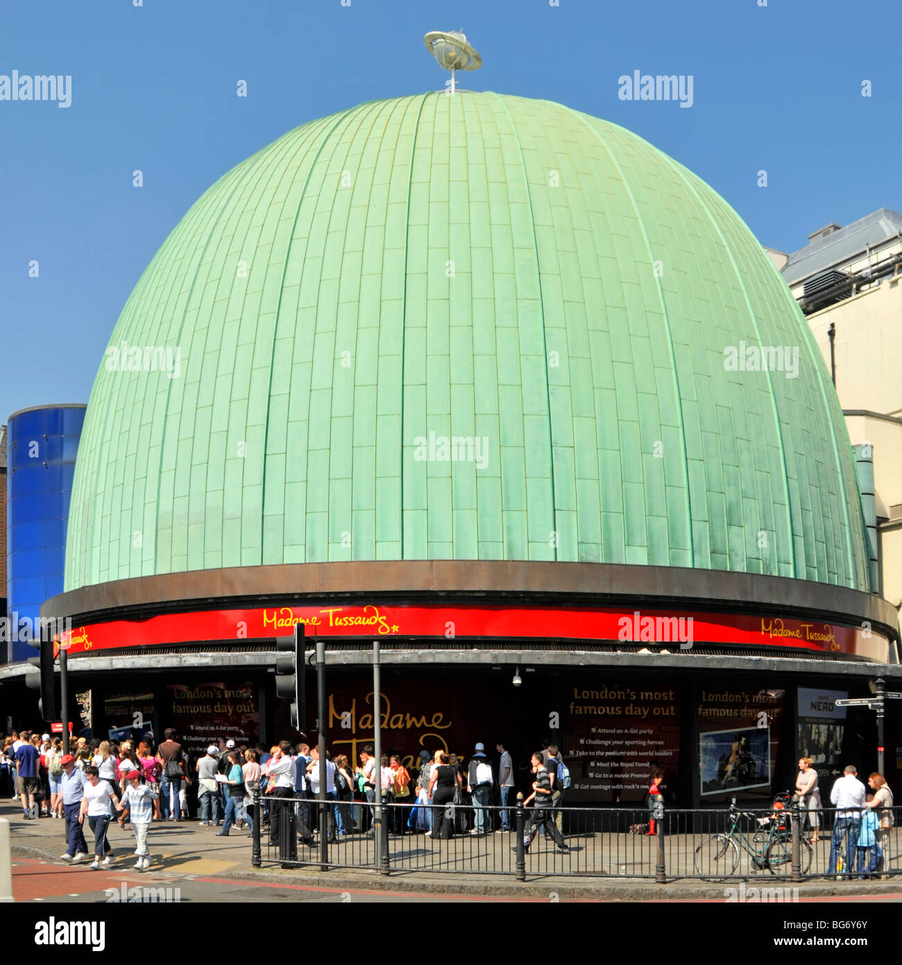 People in London street scene below green patina coating on copper roof of dome at part of Madame Tussauds Wax Museum - Stock Image