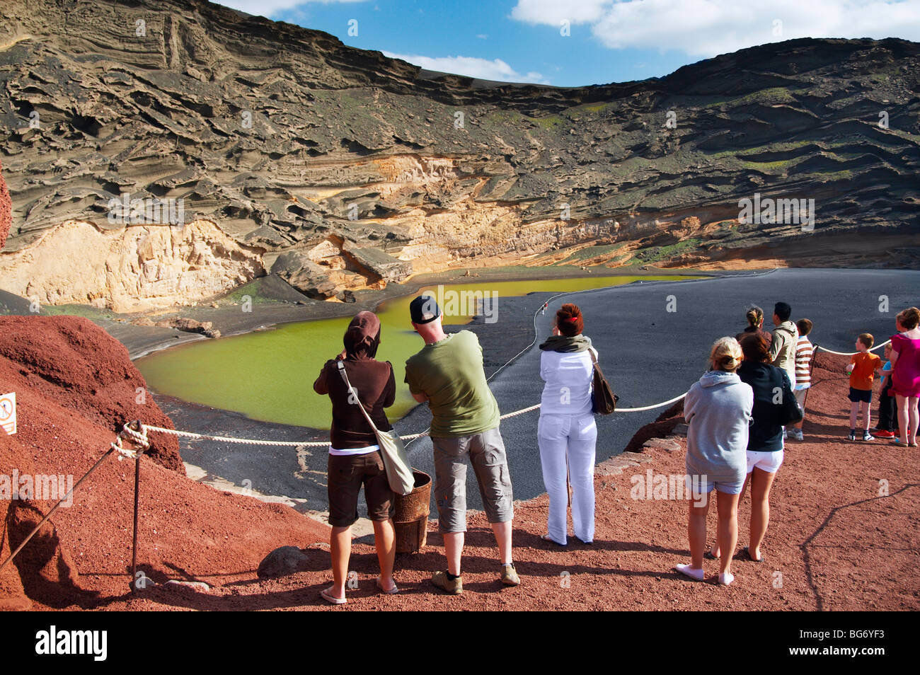Tourists at viewing point at Lago de los Clicos (green lagoon) near El Golfo on Lanzarote in the Canary islands. - Stock Image