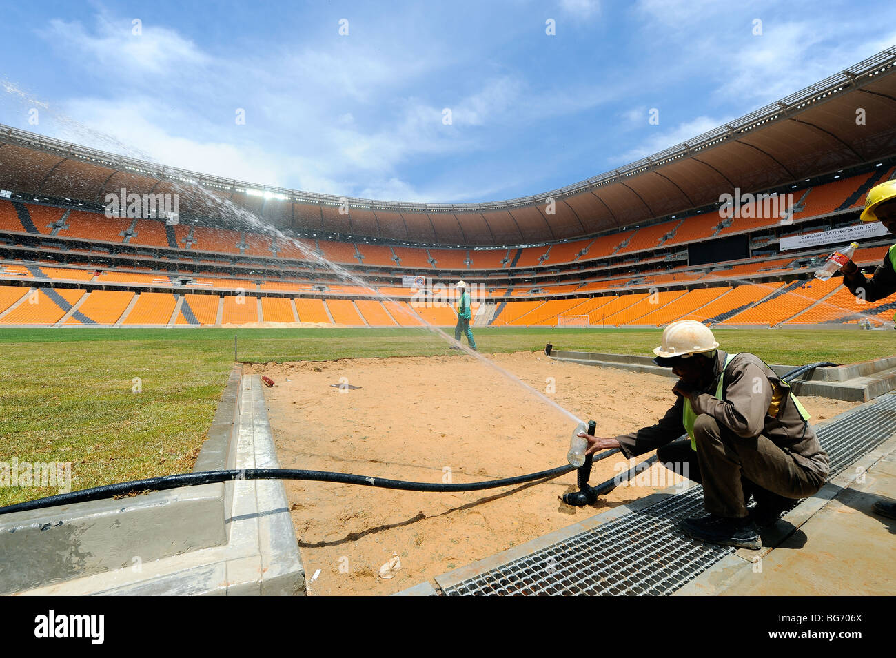 watering the pitch at Soccer City Stadium in Johannesburg, South Africa. - Stock Image