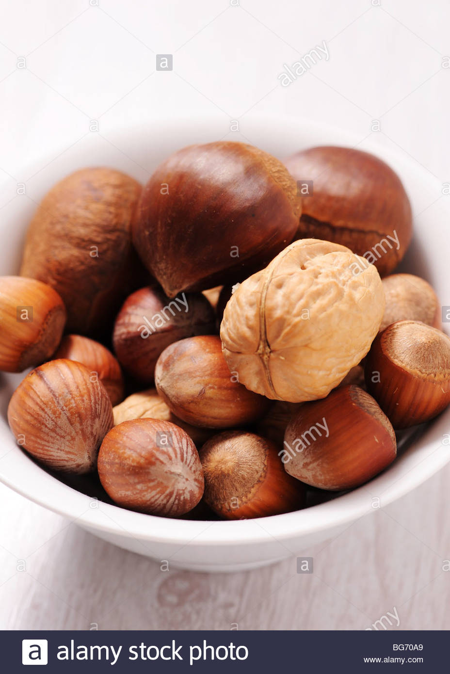 Bowl of mixed nuts on isolated background - Stock Image