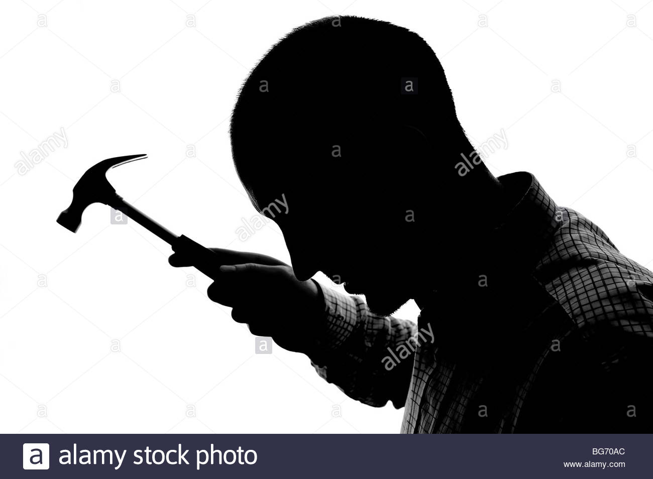 Silhouetted man with hammer - Stock Image