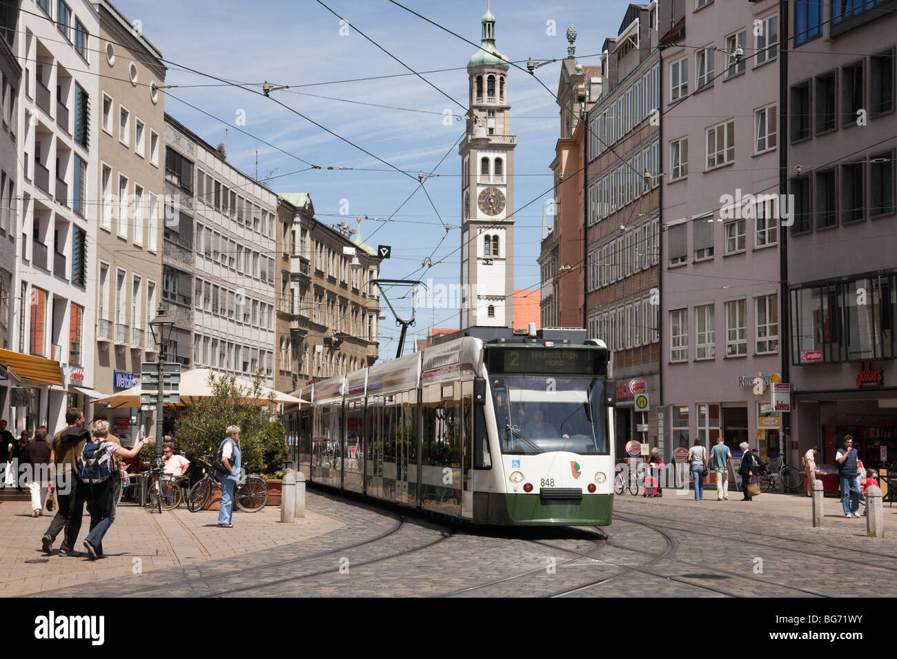 Tram on busy street in city centre with Perlachturm clock tower beyond in Maximilianstrasse, Augsburg, Bavaria, - Stock Image