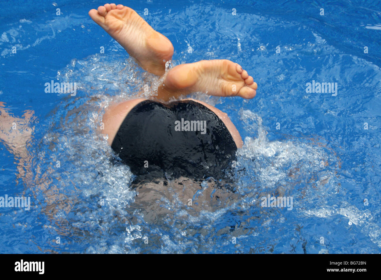 Teen Diving Into Pool With Feet Above Water Stock Photo