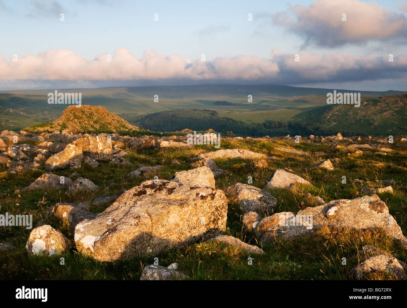 Moorland scene littered with granite rocks with Leather Tor in background, Dartmoor, Devon UK - Stock Image