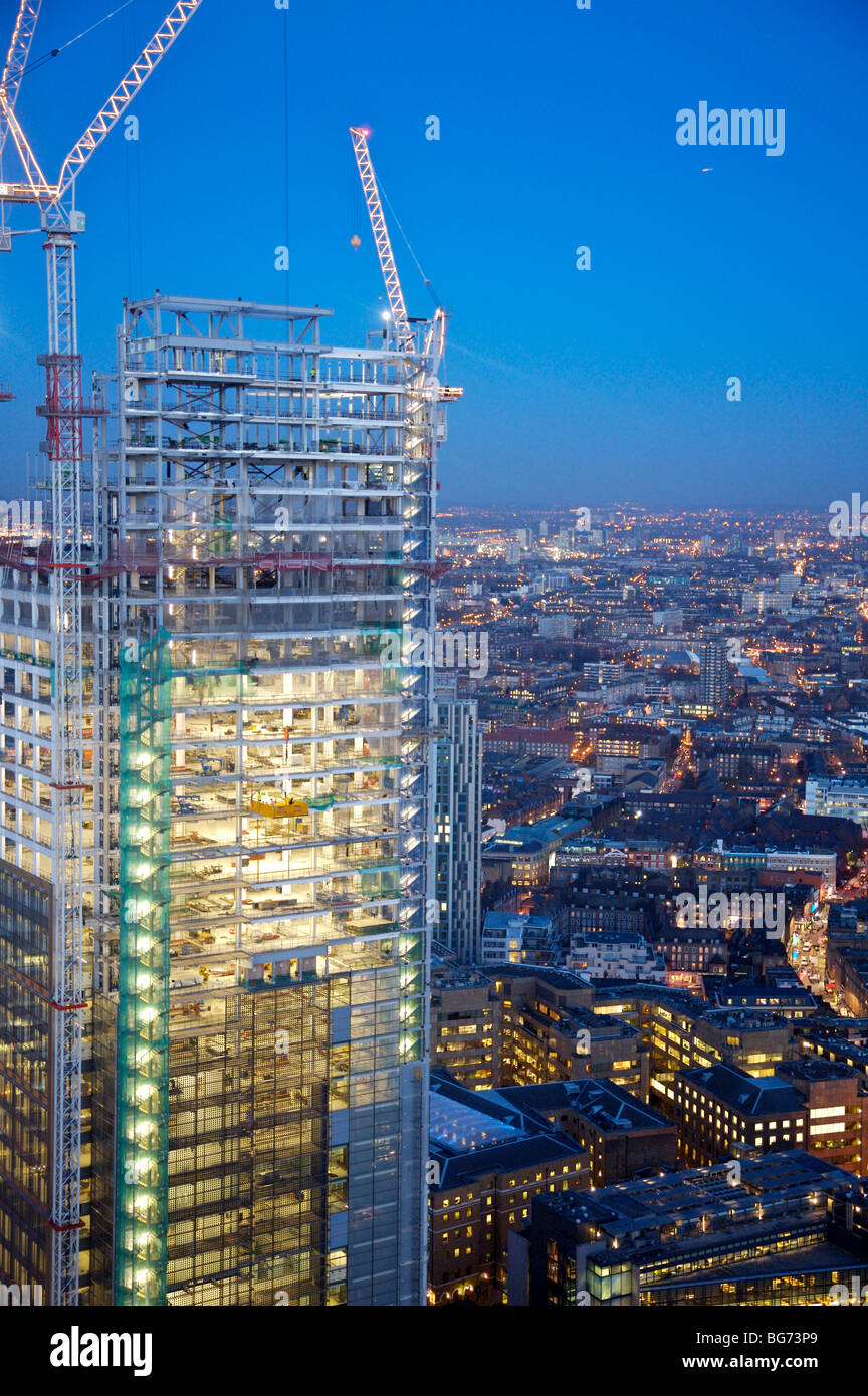 Evening aerial view from City of London looking over to East London and construction of Heron Tower with cranes - Stock Image