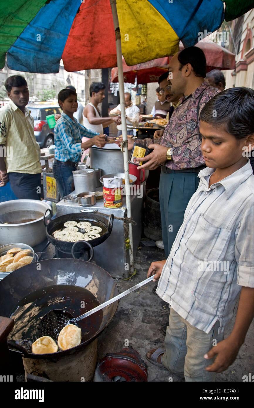 Boy frying rotis (indian bread). Calcutta (Kolkata). India - Stock Image