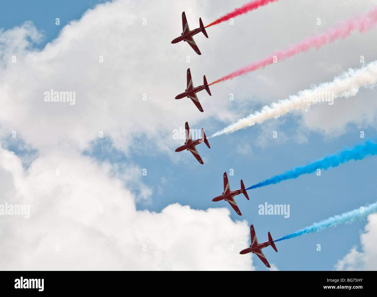 Five of the Red Arrows in formation during a flypast with coloured smoke trailing. - Stock Image