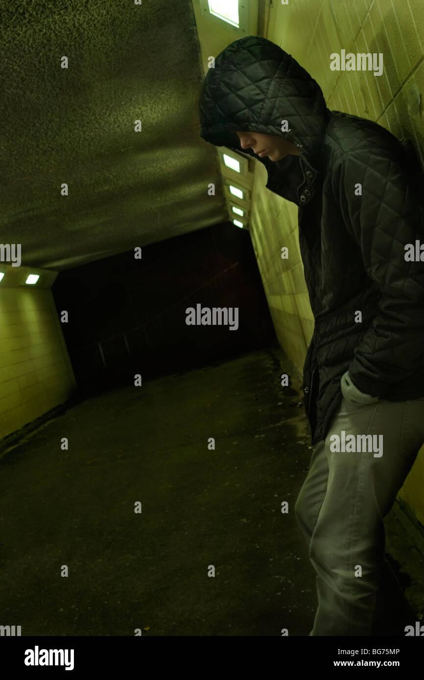 Teenage boy leaning against subway wall at night, London, UK - Stock Image