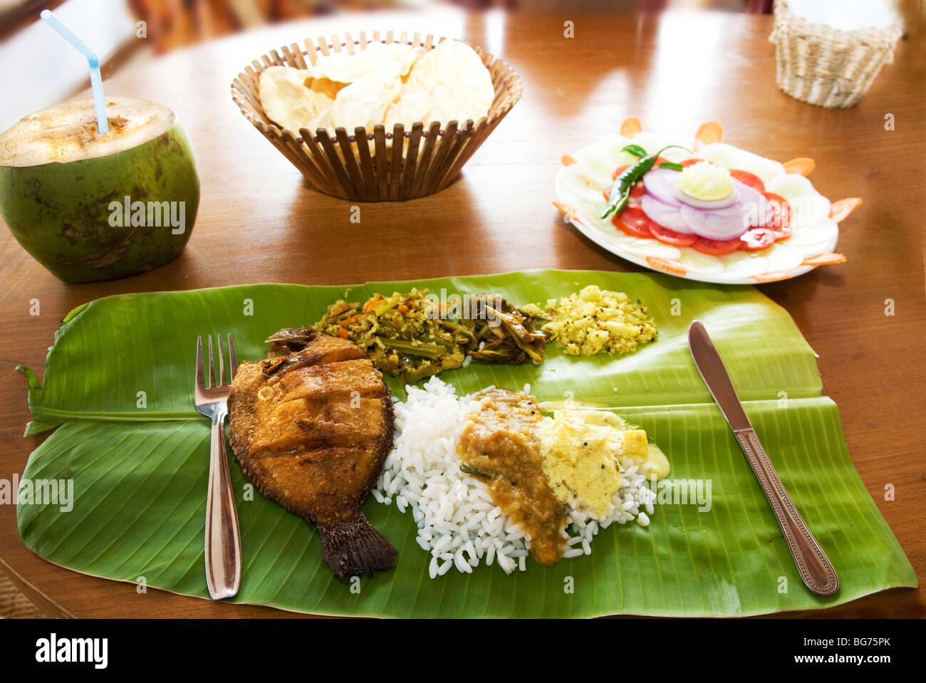 Rice Dish with fish and curry served on palm leaf,Kerala, India .Cutlery is optional to using the right hand to - Stock Image