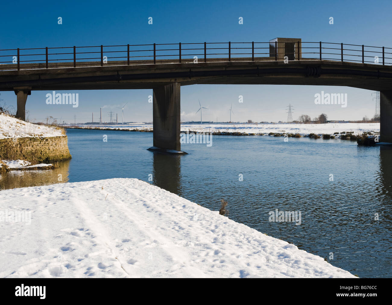 North bank of the River Nene near Peterborough, Cambridgeshire, with Whittlesey industrial area in the background - Stock Image