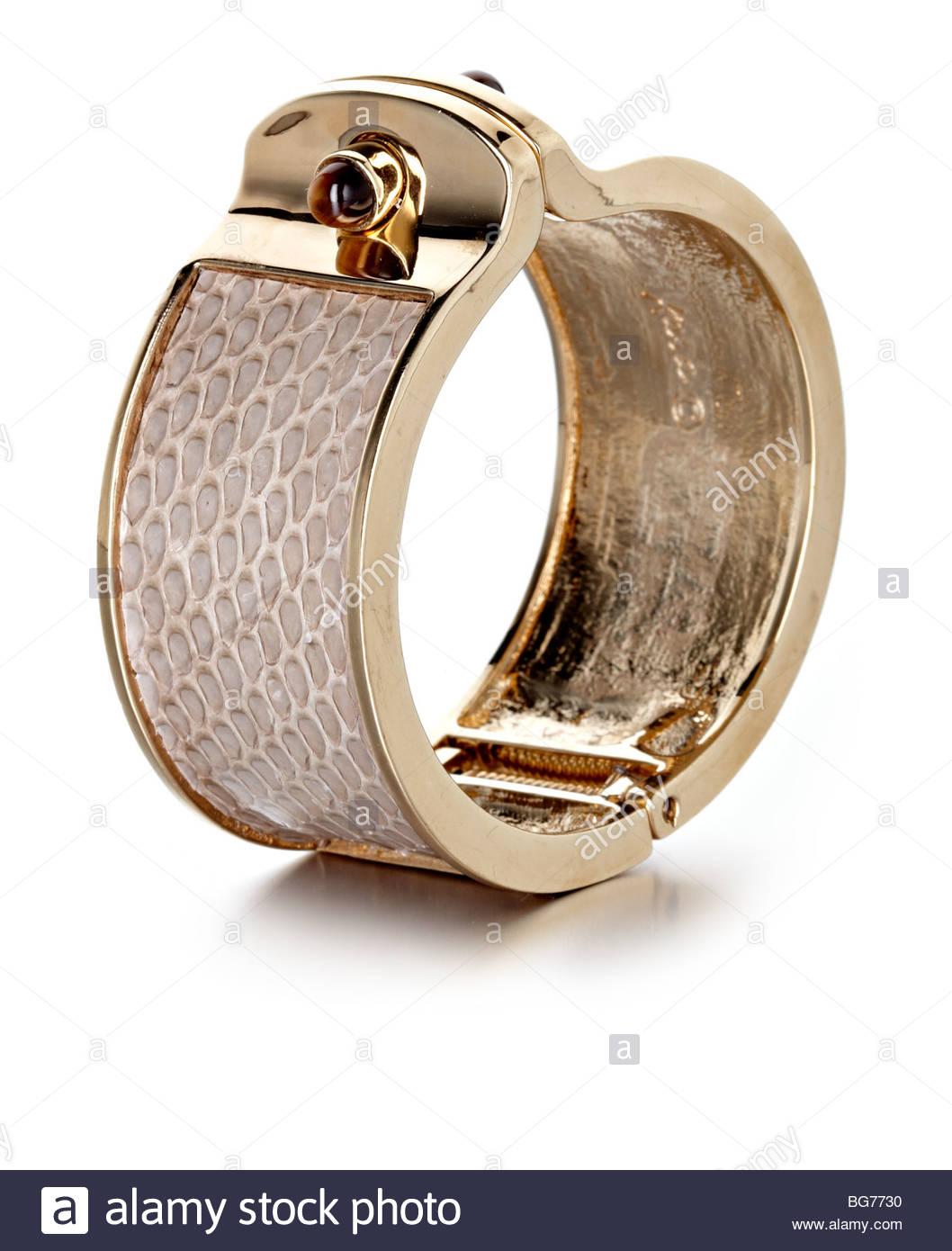 gold look metal and snake skin bangle - Stock Image
