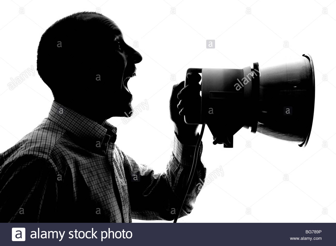 Silhouetted man with loudhailer - Stock Image