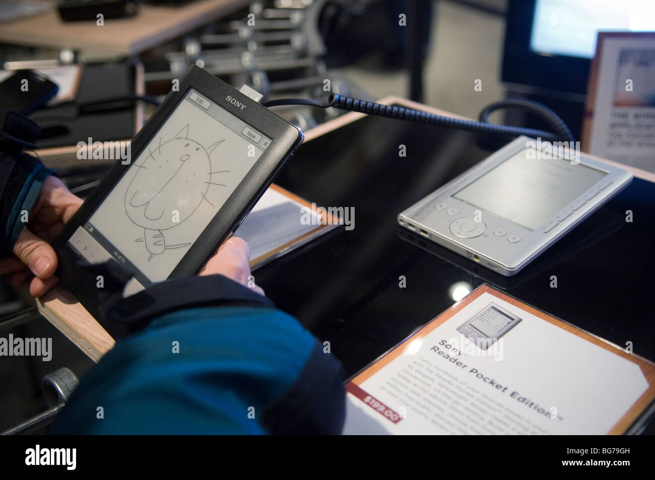 A customer at the Wired pop-up store store in New York examines a Sony Reader Touch Edition ebook reader - Stock Image