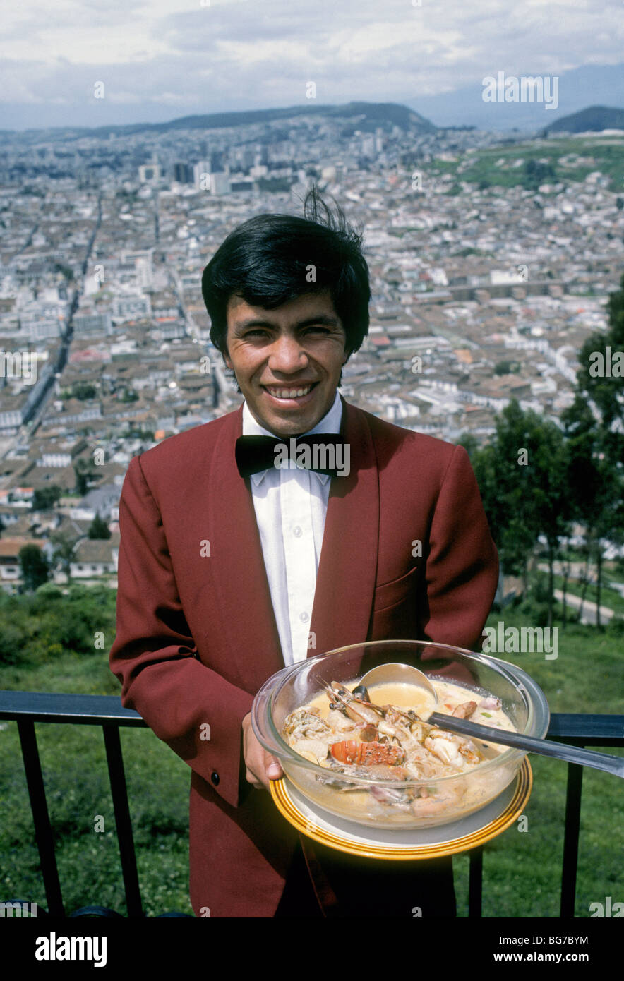 A waiter at an expensive restaurant in Quito, Ecuador, serves up a large bowl of seafood soup - Stock Image