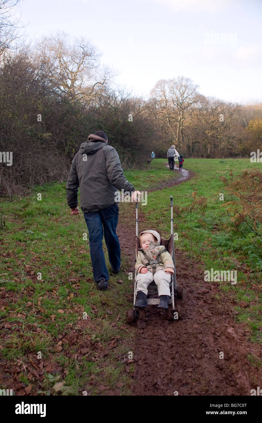 Dragging a young child in buggy through the mud at Occombe farm 2km easy-access nature trail which runs through - Stock Image