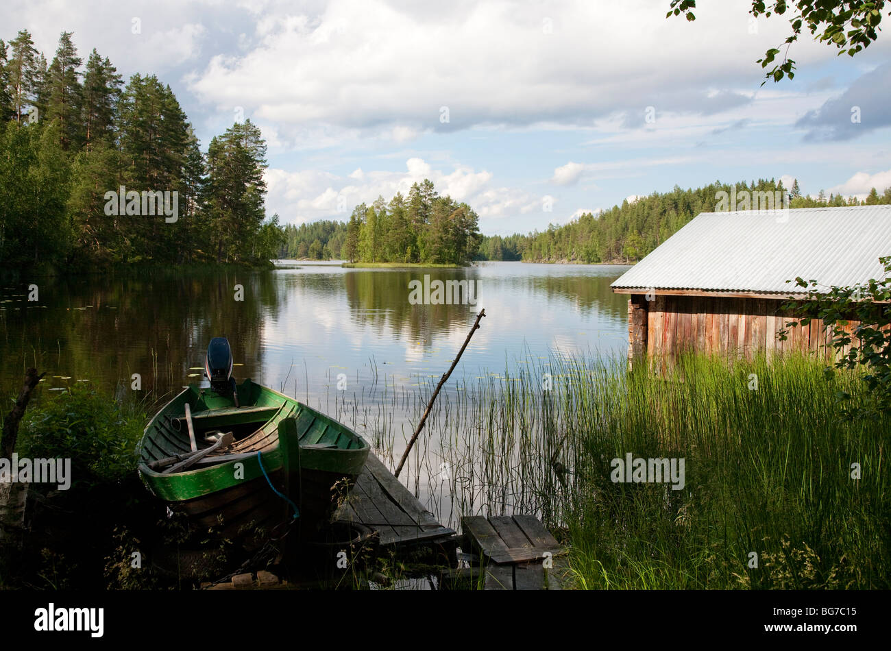 Old Finnish boathouse  , made of logs ,  and a wooden rowboat at lake Konnevesi shore , Finland Stock Photo