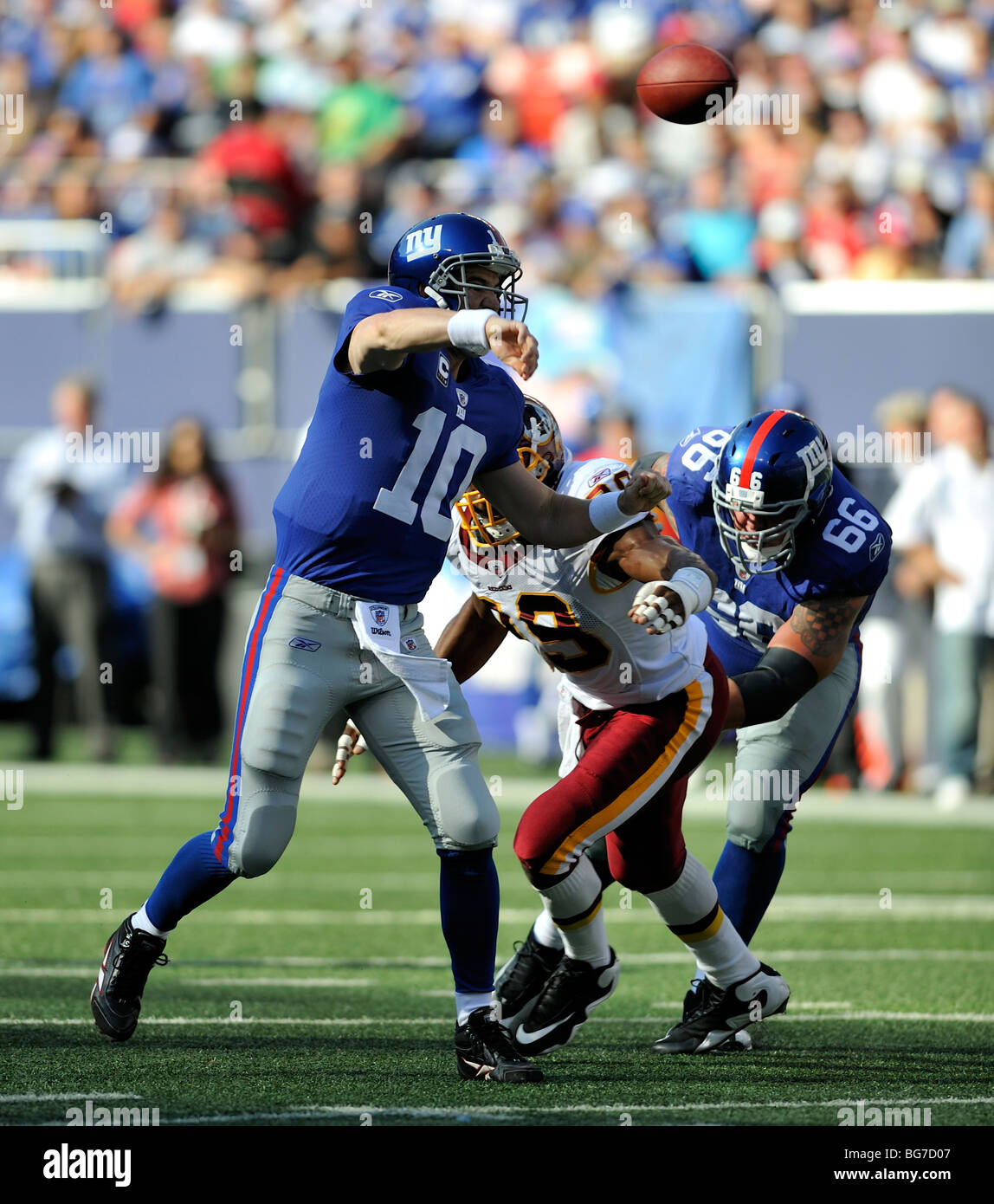 Eli Manning of the New York Giants gets the pass away while under pressure from the Washington Redskin defense - Stock Image