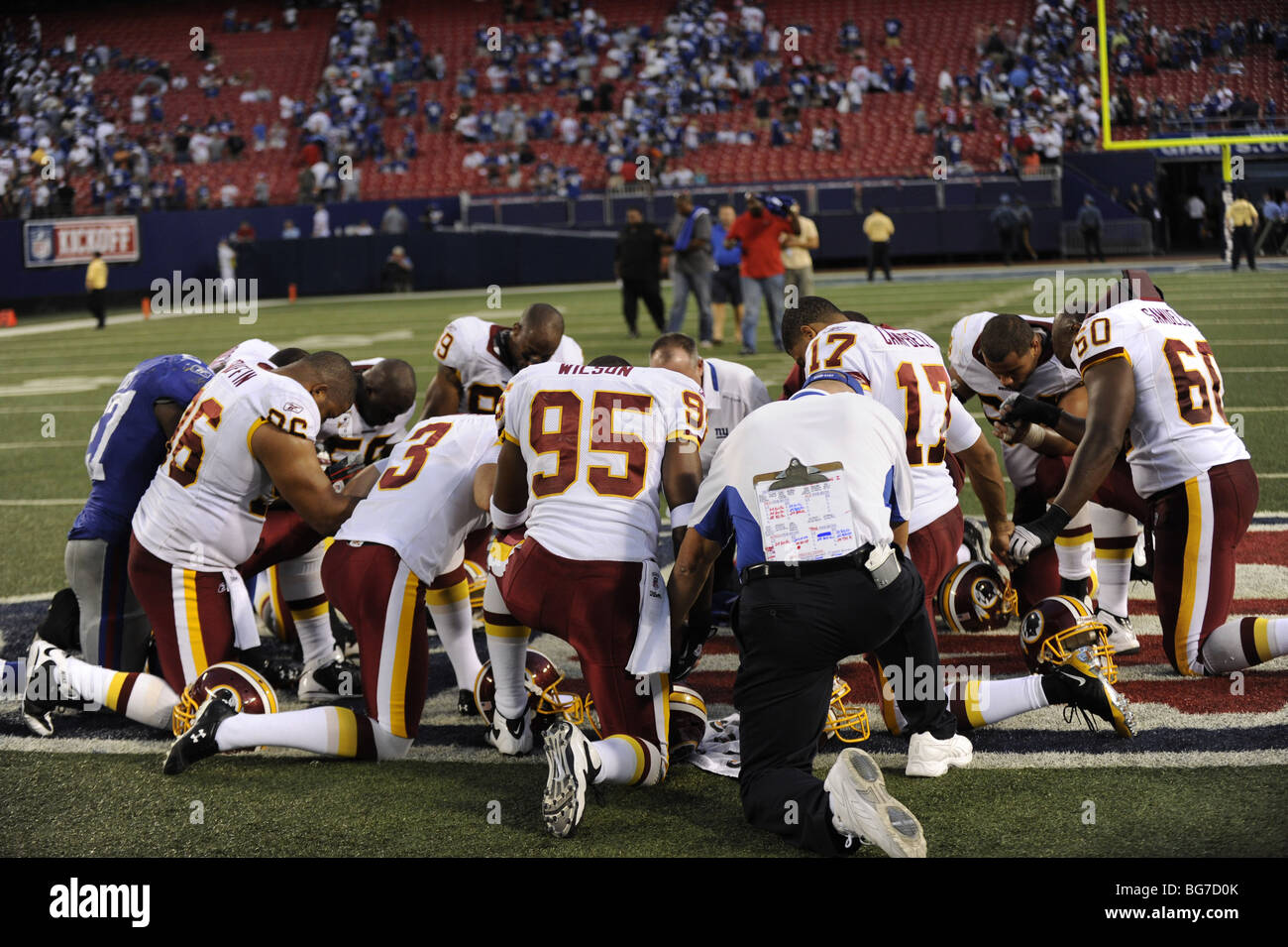 Professional football players pray on the field after a game - Stock Image