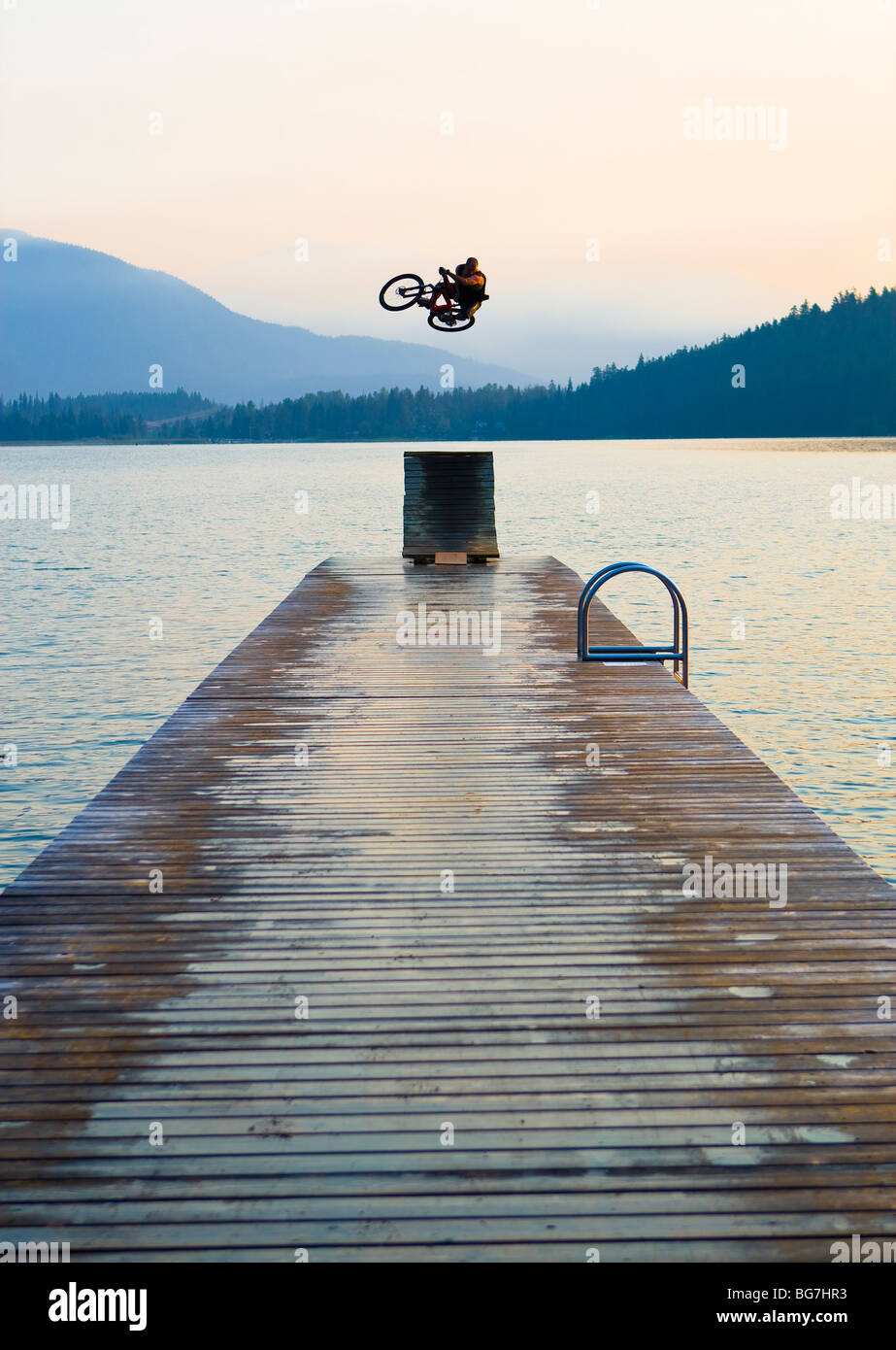 A freestyle mountain bike rider practices high risk tricks off a jump ramp on a dock into a lake. - Stock Image