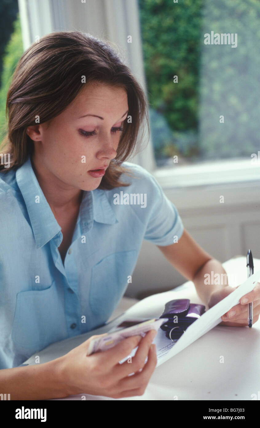 young woman with credit cards looking worried - Stock Image