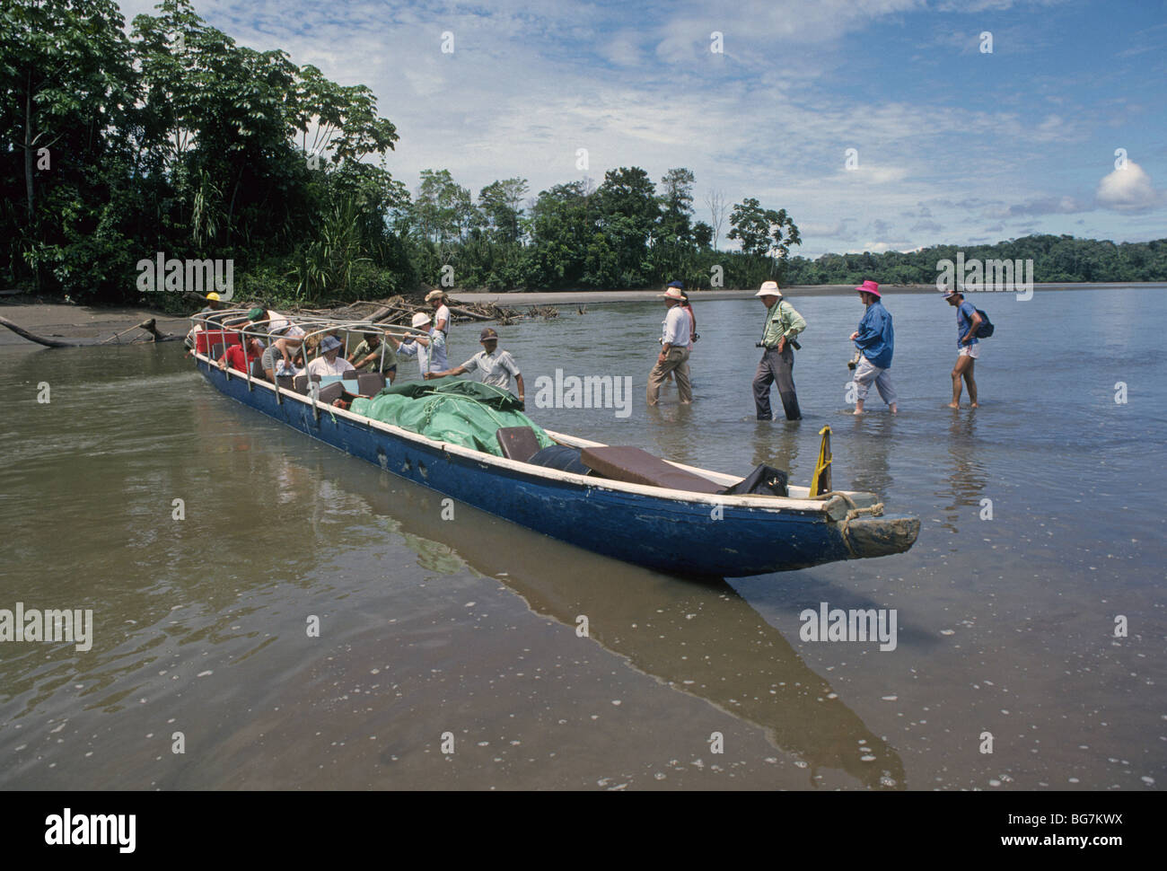 American adventurers on photo tour board a large dugout canoe for a trip down the Napo River in the Amazon Basin, - Stock Image