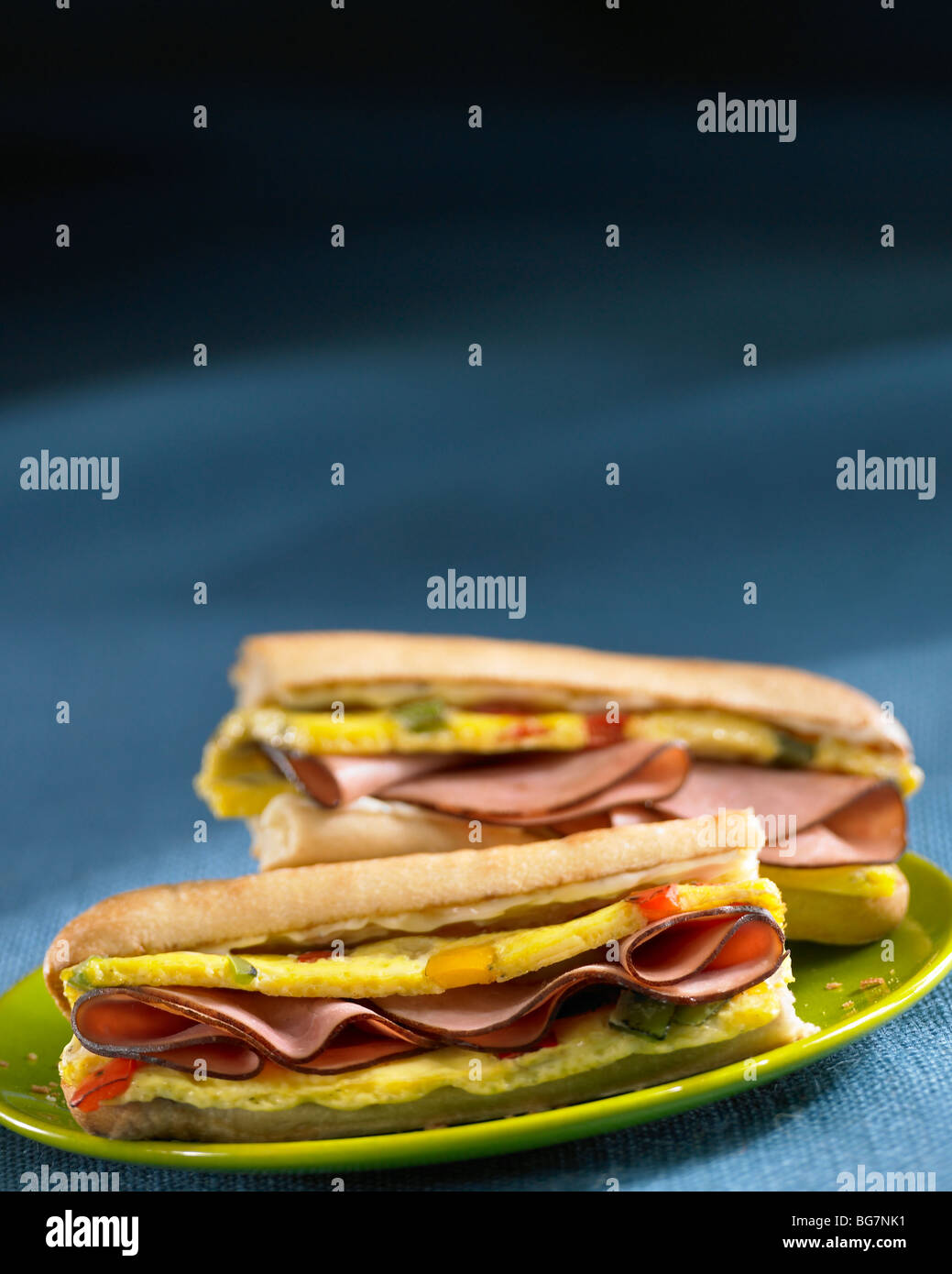 Ham and egg breakfast sandwiches on green plate - Stock Image