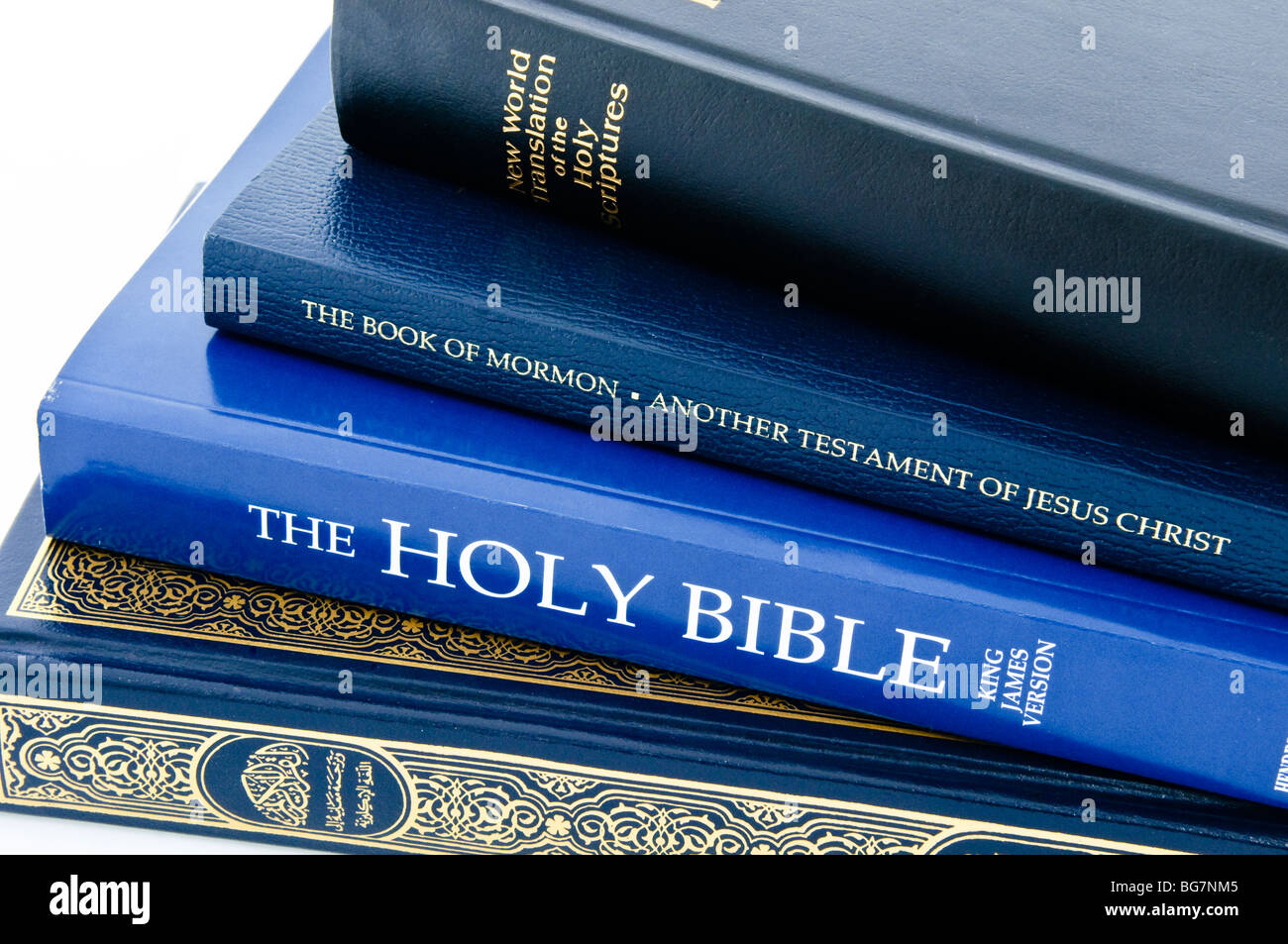 Stack of holy books - New World Translation of the Holy Scriptures, Book of Mormon, Holy Bible and the Qu'ran - Stock Image