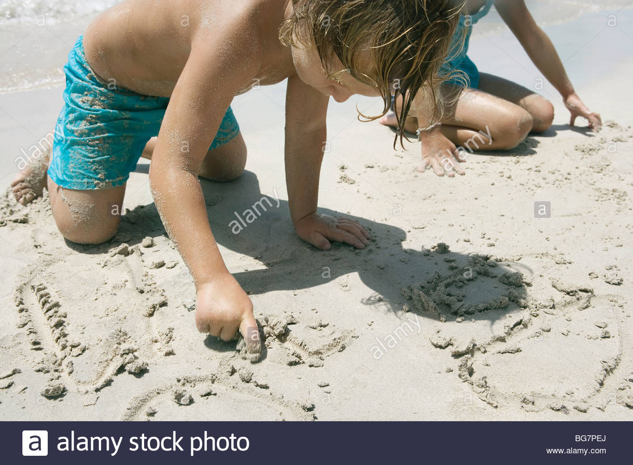 Boy and girl writing in sand on beach - Stock Image