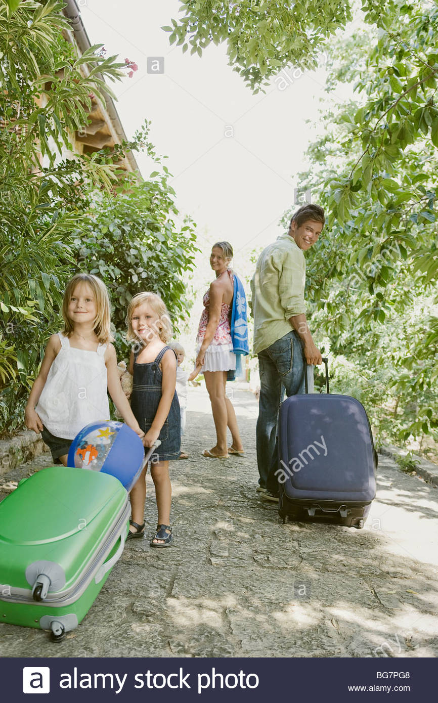 Family with suitcases on walkway - Stock Image