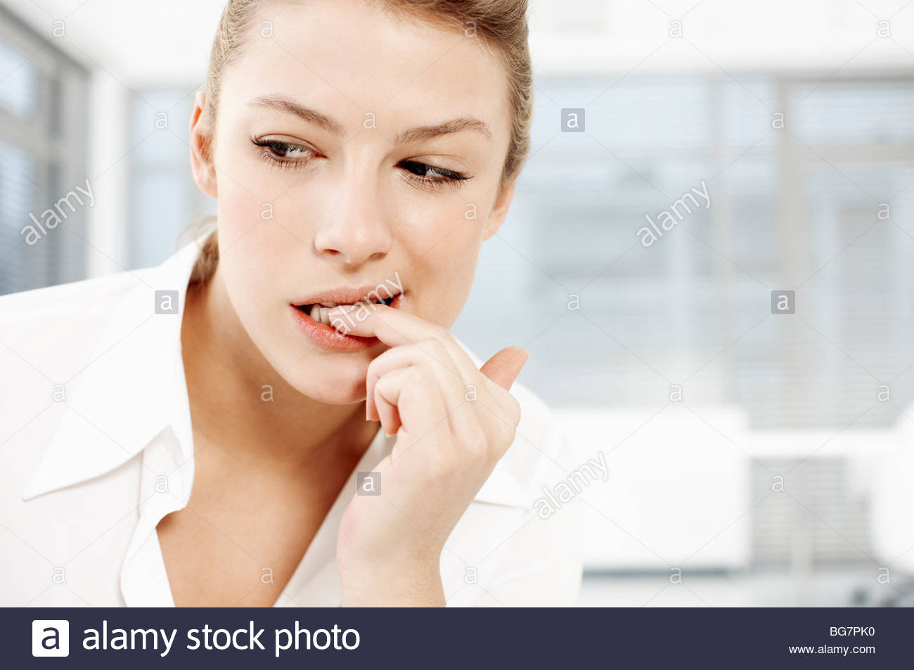 Businesswoman biting fingernails - Stock Image