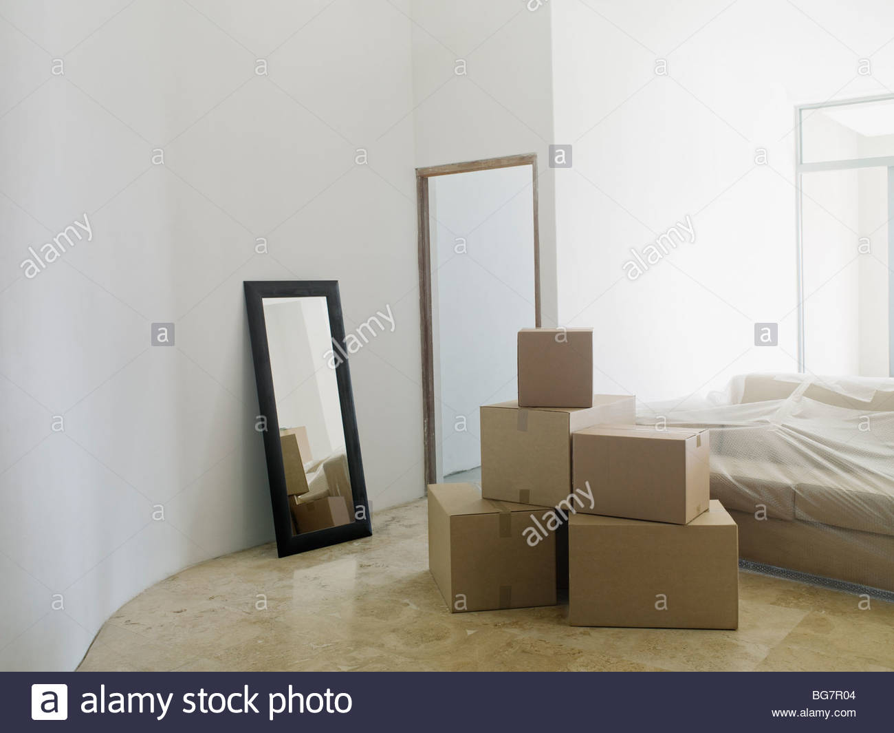 Cardboard boxes and mirror in new house - Stock Image