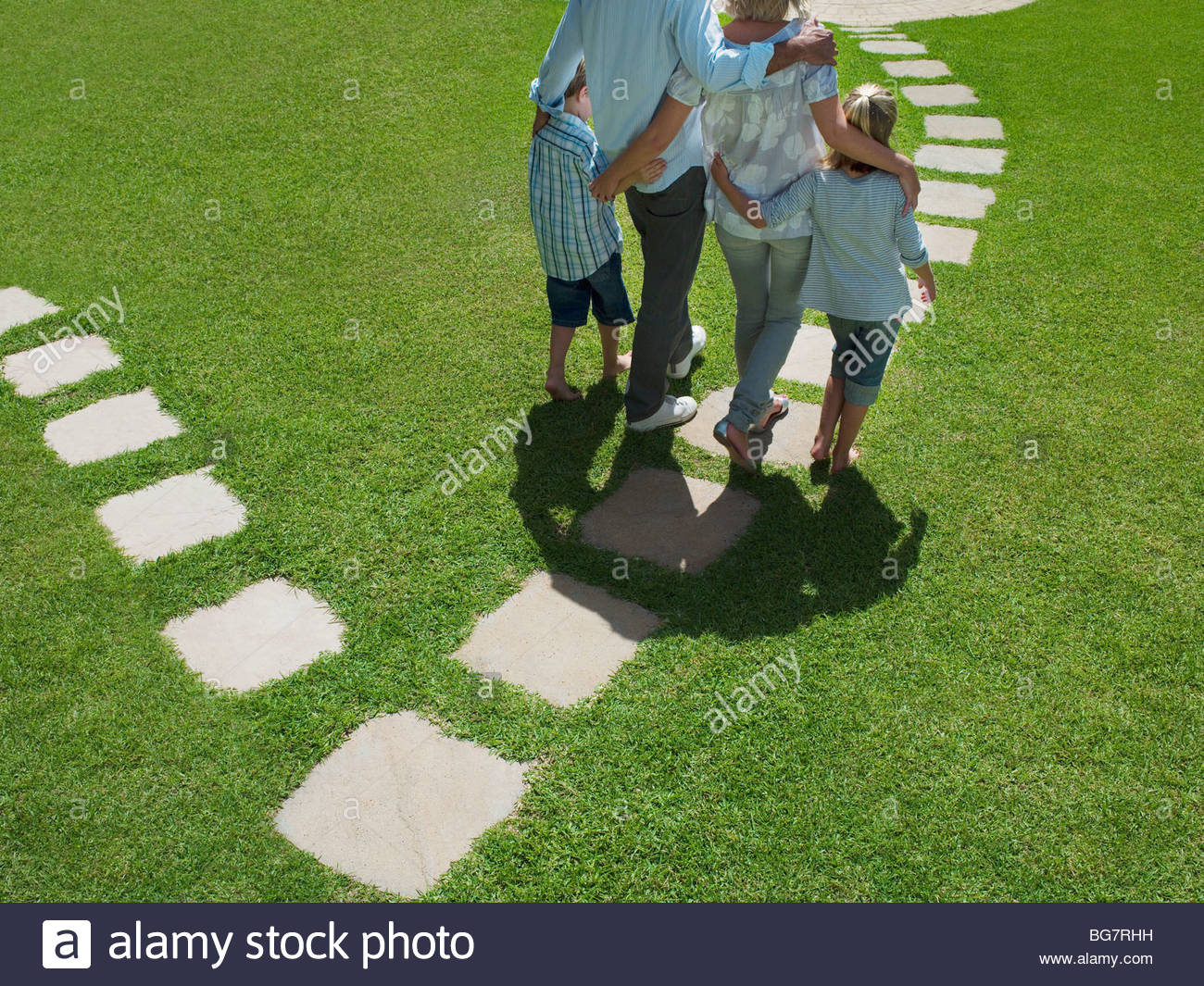 Family walking on stones in grass - Stock Image