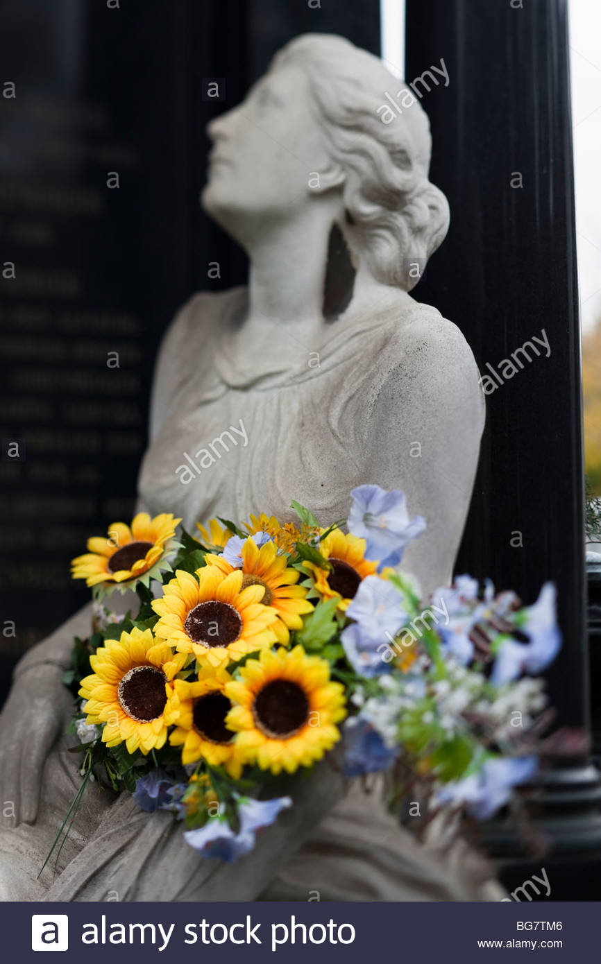 grave, marble statue, sunflowers - Stock Image