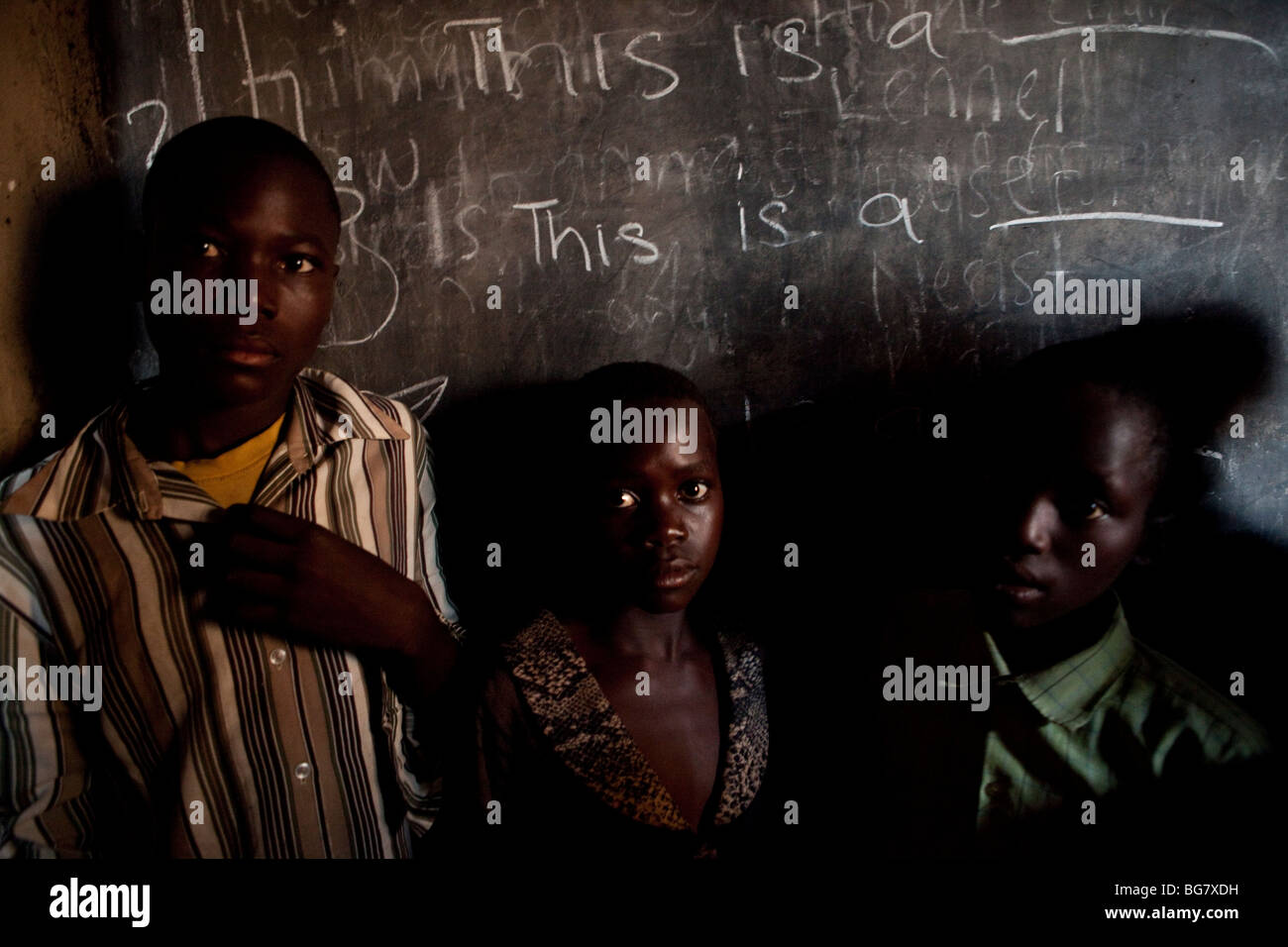 Children stand in front of a blackboard in a classroom in Amuria, Uganda. - Stock Image