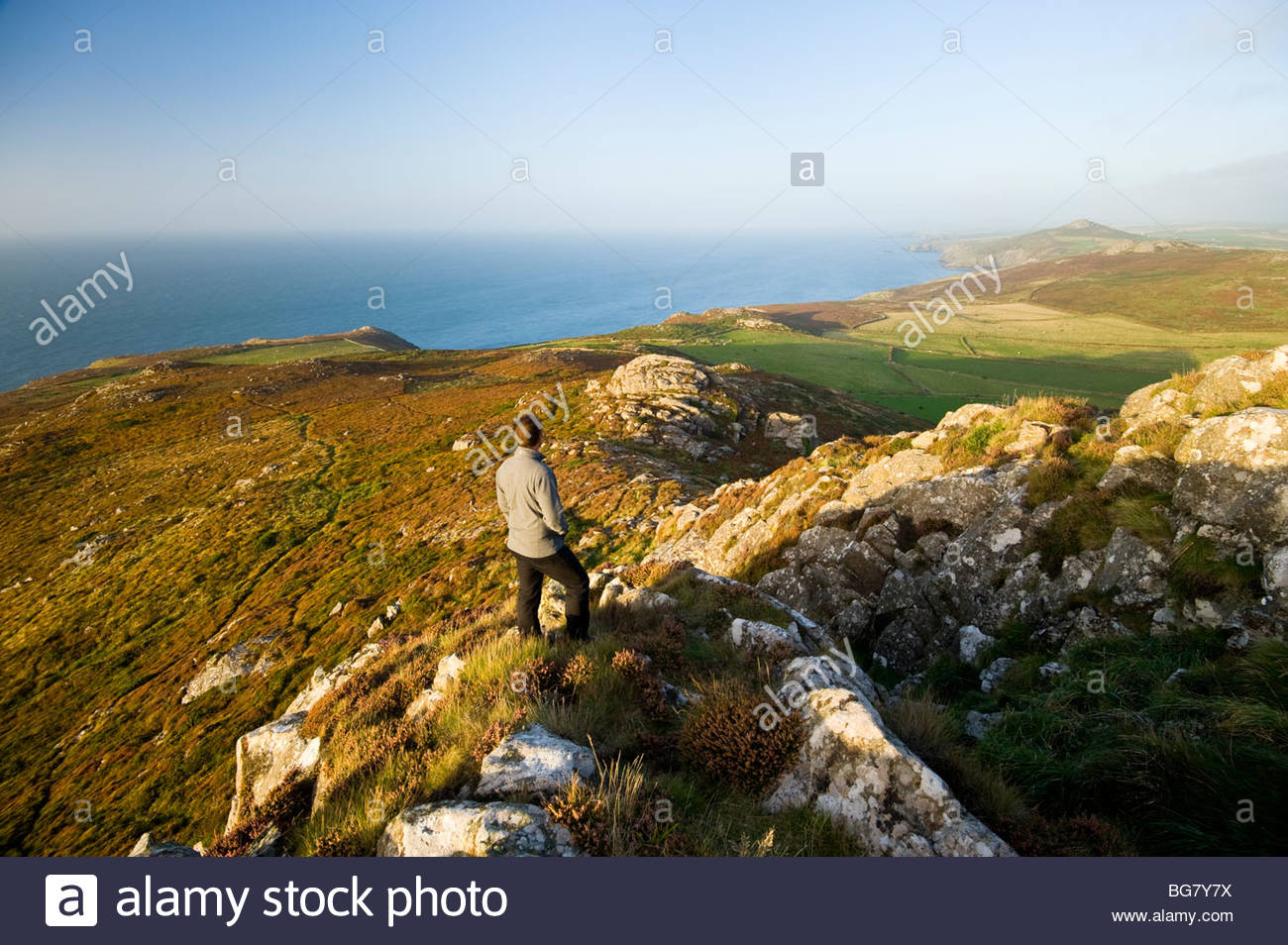 Walker looking North East from the summit of Carn Llidi, Pembrokeshire, South Wales. - Stock Image
