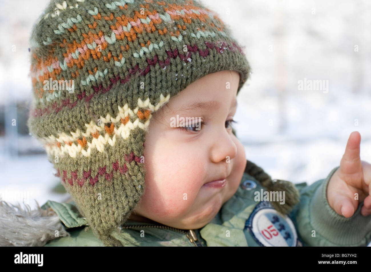 11 month old Hispanic boy plays in fresh fallen snow in his front yard with his mother. Image is model released. - Stock Image