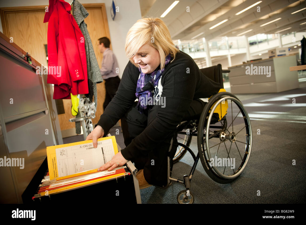 Young disabled woman in a wheelchair working filing documents in a modern office, Uk - Stock Image