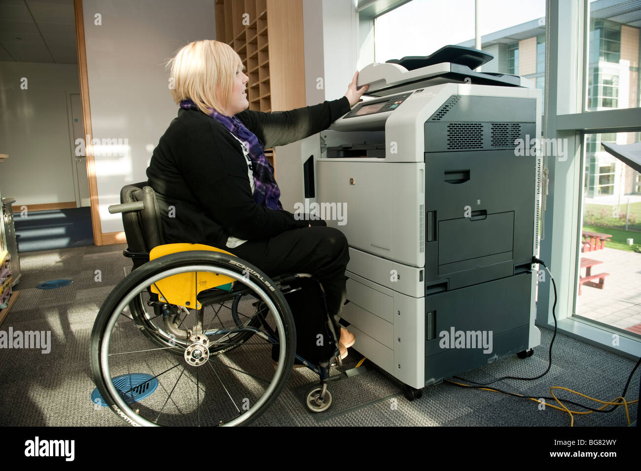 A young disabled woman in a wheelchair working using a photocopier machine in a modern office, UK - Stock Image