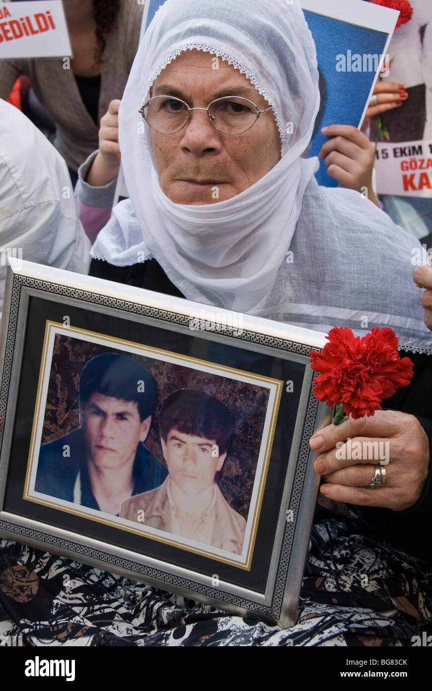 KURDISH WOMAN HOLDING A PICTURE OF HER DISAPPEARED SON WHILE UNDER POLICE INTERROGATION AND CARNATION - Stock Image