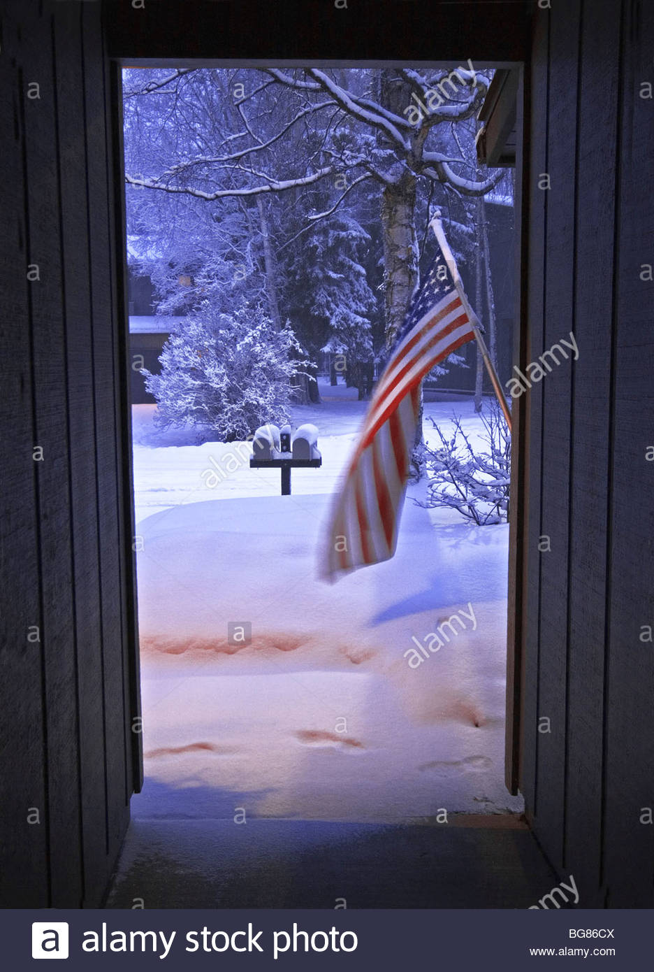 View from front door of townhouse in Anchorage, Alaska in January with snow and American flag. - Stock Image