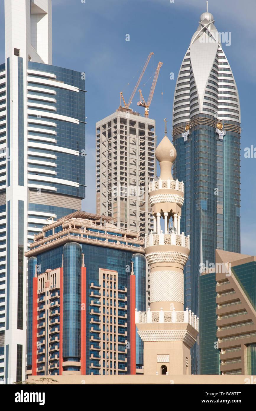 Dubai mosque minaret against sky scrapers - Stock Image