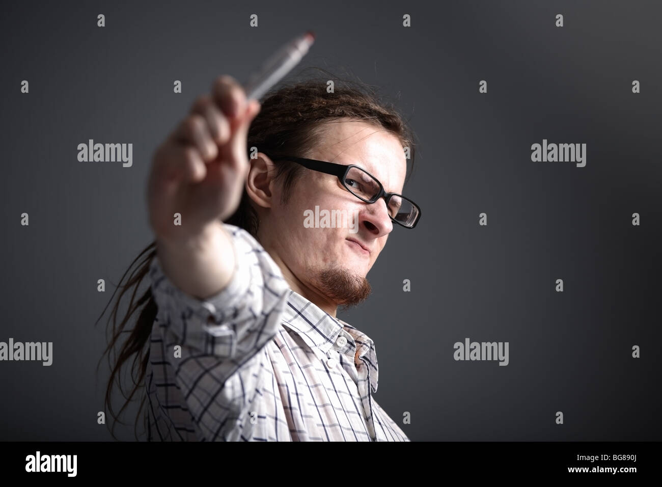 longhaired eccentric man in glasses makes a gesture of holding a marker - Stock Image